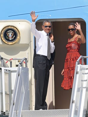 President Barack Obama and Michelle Obama wave before boarding Air Force One to depart Palm Springs, Monday, June 16, 2014.