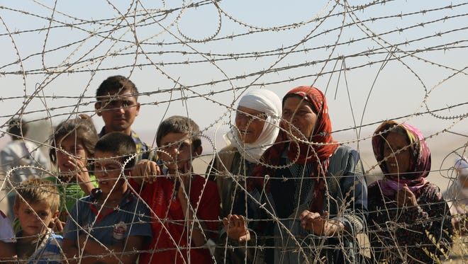 A family stands near a fence Sunday as several hundred Syrian refugees wait to cross into Turkey at the border in Suruc, Turkey. Americans have been hotly debating whether the United States should allow Syrian refugees into the country following terrorist attacks in Paris.