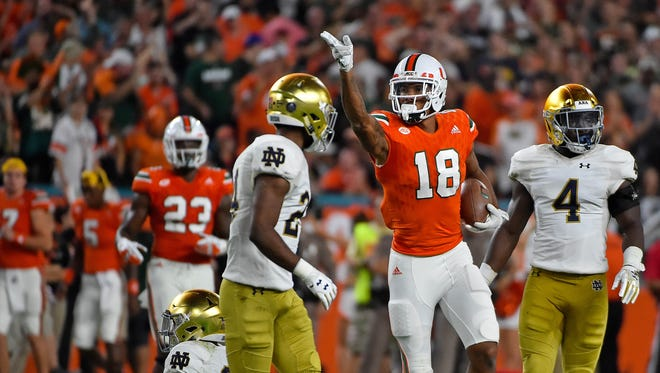 Miami Hurricanes wide receiver Lawrence Cager (18) signals for a first down after running the ball against the Notre Dame Fighting Irish during the first half at Hard Rock Stadium.
