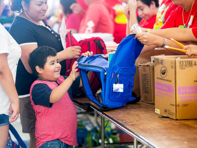 Eli Alonso, 4, smiles as volunteers fill his new backpack