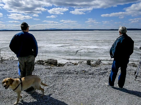 Bystanders looked at the scene after wo people walked across the ice and made it to shore after their small plane went down on the ice of Lake Champlain near Savage Island on Saturday, April 11, 2015.