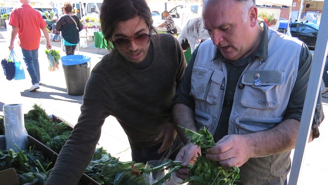 Chef Jose Andres, right, examines a head of puntarelle at the Tutti Frutti Farms booth at the Ventura County Certified Farmers' Market in downtown Ventura.
