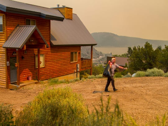 A resident of Panguitch Lake carries belonging out