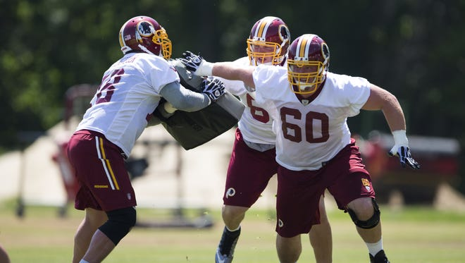 """Washington Redskins rookie guard Spencer Long, right, tackle Tom Compton, center, and center Kory Lichtensteiger take part in drills during an NFL football practice at Redskins Park, on June 4 in Ashburn, Va. A ruling from the U.S. Patent Office on Wednesday canceled the team's trademark registration that included the name """"Redskin."""""""