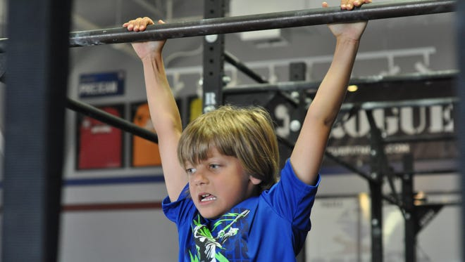Reeves Scroggs, 7, swings on monkey bars while completing an obstacle course during his weekly CrossFit Kids workout.