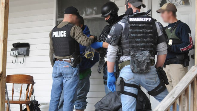 Drug Task Force looks through the personal items of a person of interest who was on the porch of a house that was raided on Sixth Street in 2012 in Port Huron.