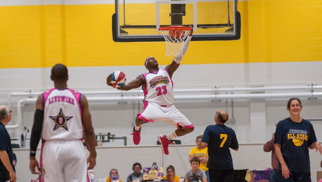 A member of the Wizards grabs the rim for a dunk Monday, Oct. 3, during the opening of the Fieldhouse community All-Star game against the Harlem Wizards.