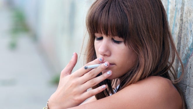 Teenage girl smoking cigarette.