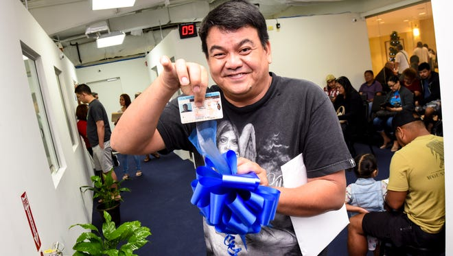 Merizo resident Deogracias Lazo proudly displays a blue ribbon and his driver's license while at the Guam Department of Revenue and Taxation's satellite office in the Agana Shopping Center on Friday, Dec. 1, 2017. Lazo saved the ribbon from the ribbon cutting ceremony to celebrate the opening day of the department's new customer service outlet and the license was the first one to be issued at the venue. However, agency Deputy Director Marie Benito said the orientation of the photo wasn't right and he may have to be called back.
