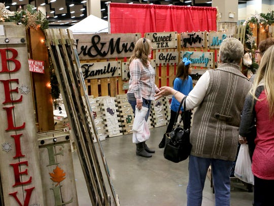 A group of customers look through a booth featuring decorative signs Saturday afternoon during Hanger Holiday at the Multipurpose Events Center.