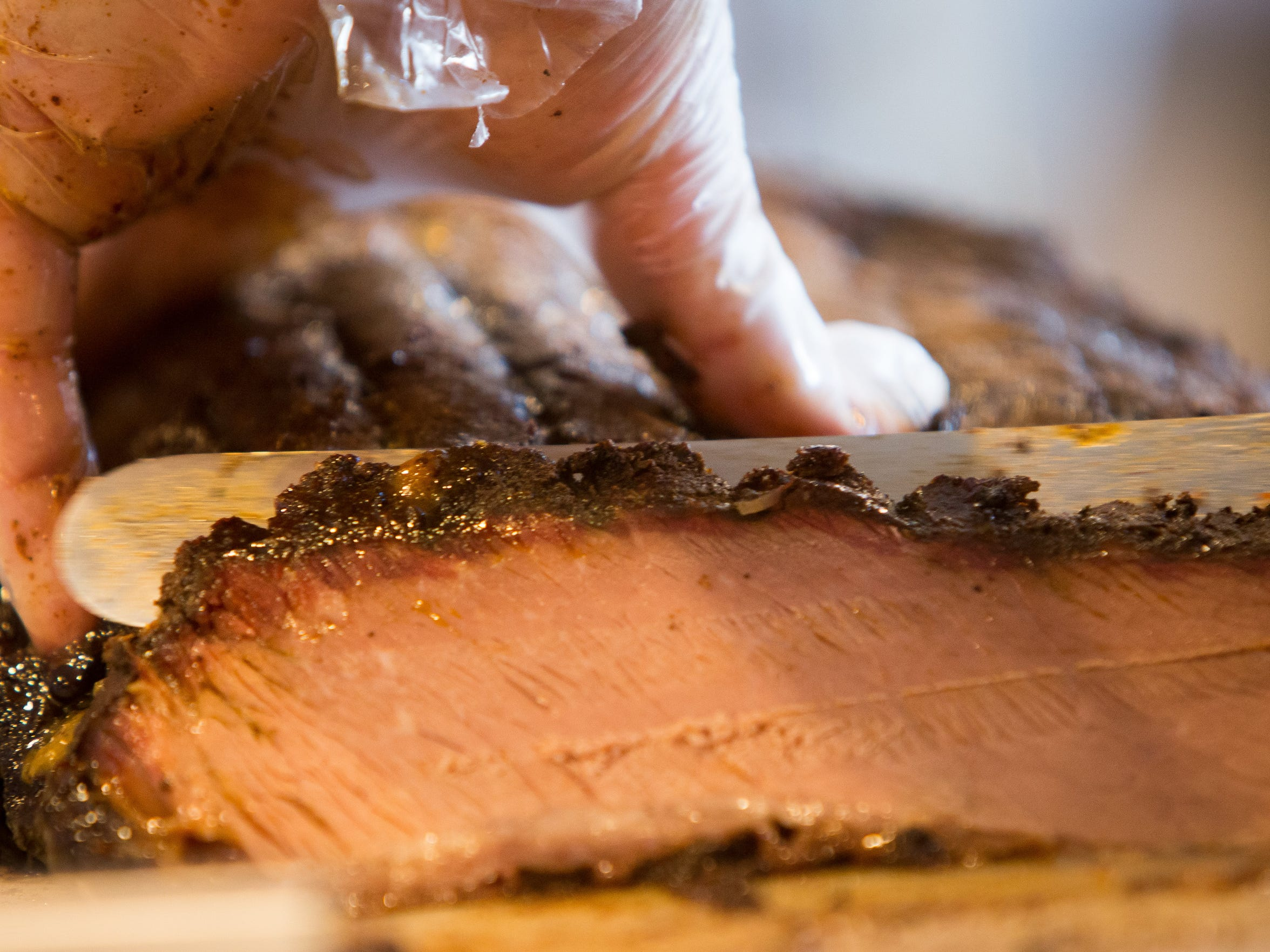 Locale BBQ Post's Chris Baittinger slices slow-cooked brisket. The Wilmington barbecue shop will be at the Historic New Castle Colonial BBQ Competition.