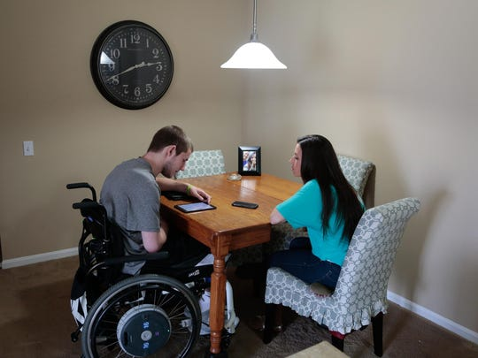 Chris Norton looks over items on a tablet while sitting with his fiancee Emily Summers at their apartment in Northville, Mich., on June 5, 2015. Norton broke his neck in a college football game in 2010 while playing at Luther College. He was given a three percent chance to walk again, but has worked and gritted through and can walk with minor assistance. Norton and his fiancee moved to Michigan to work at Barwis Methods in Plymouth to continue his recovery.