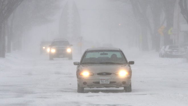 Drivers use their lights and drive slowly in blizzard-like conditions on South 8th Street in Sheboygan on Sunday.