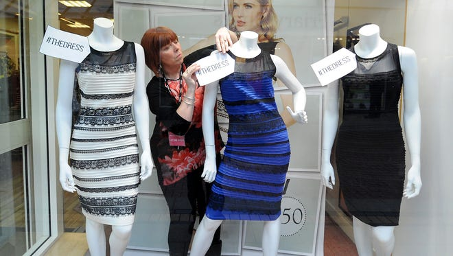 Shop manager Debbie Armstrong adjusts a two tone dress in a window display of a shop in Lichfield, England, Friday Feb. .27, 2015. It's the dress that's beating the Internet black and blue. Or should that be gold and white? Friends and co-workers worldwide are debating the true hues of a royal blue dress with black lace that, to many an eye, transforms in one photograph into gold and white.