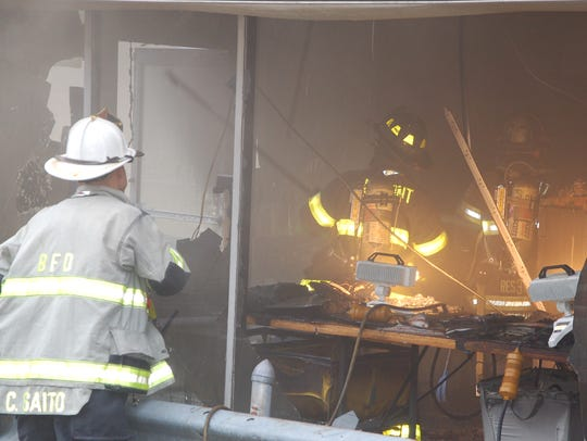 Firefighters begin to inspect the interior of the Laundromat after extinguishing the blaze.