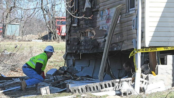 Investigators from the state fire marshal's office and workers from Columbia Gas look for the cause of a weekend explosion at 613 Fleming Falls Road.