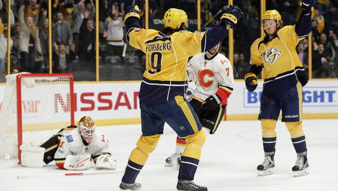 Nashville Predators left wing Filip Forsberg (9) celebrates with Ryan Johansen, right, after Forsberg scored his third goal of the night against Calgary goalie Brian Elliott, left, during the second period on Feb. 21, 2017.