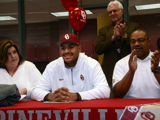 Pineville High School offensive tackle Cody Ford (center) is all smiles after signing a national letter of intent to play football at Oklahoma in 2015. Ford was drafted by the Buffalo Bills in the second round of the 2019 NFL Draft Friday. With Ford are his parents Leah Ford (left) and Robert Ford (far right) and principal Karl Carpenter.