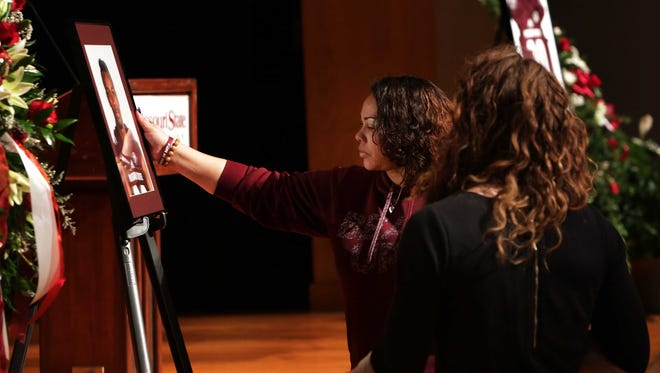Roxanne Bruce touches the portrait of her son, MSU football player Richard Nelson, who was shot to death while protecting his sister in Las Vegas, at the end of a memorial service honoring him.