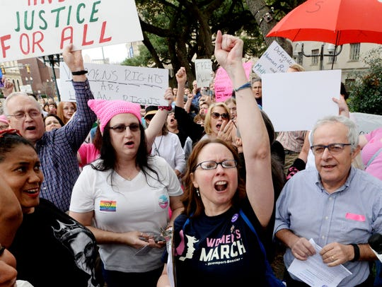 Debbie Hollis (center) marches and chants during the