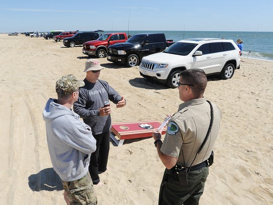 DNREC Chief of Enforcement Wayne Kline talks with surf fisherman Rick Boulware and John Fleming from Middletown about new single file parking rules on the beach at Cape Henlopen State Park near Lewes on Saturday May 23rd.CHUCK SNYDER/Special to the News Journal
