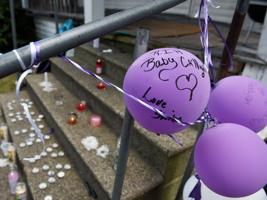 Balloons are tied to the porch railing beside a makeshift