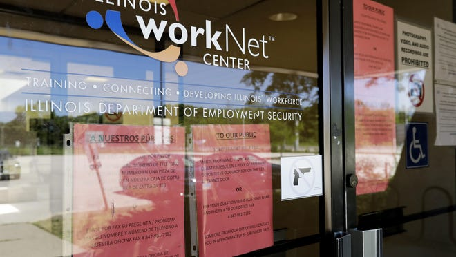 In this June 11, 2020 file photo, information signs are displayed at the closed Illinois Department of Employment Security WorkNet center in Arlington Heights, Ill. U.S. businesses sharply reduced hiring July 2020, in a sign that the resurgent viral outbreak this summer slowed the economic recovery as many states closed parts of their economies again and consumers remained cautious about spending.