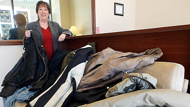 Candy Barnes, of Century 21 LeMac Realty East, shows coats collected at the office for the RPAC coat drive.