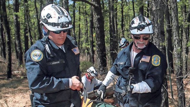 "NJ Task Force 1 team members, Matt Johnson, left, and Dale Gentek, carry a ""victim,"" freed from a called tree, during Operation Derecho, a full-scale search and rescue exercise hosted by the NJ State Office of Emergency Management at Fort Dix on April 17, 2016."
