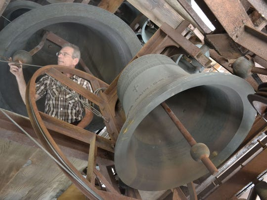 Greg Keiler, the longtime carillon maintenance worker at First Evangelical Lutheran Church in Green Bay, inspects some of the 47 bronze bells that are encased in the carillon tower atop the church. First Evangelical is one of only three recognized sites in Wisconsin that have a carillon.