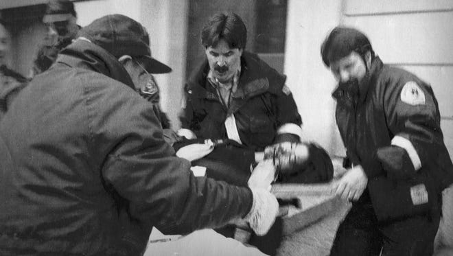 A survivor is tended to in the 1991 shootings at the University of Iowa in which Gang Lu killed five people.