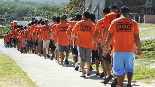 Detainees march in line to the dining hall for their dinner at the Department of Corrections in Mangilao in this March 2010 file photo.