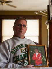 Mike Bogan, of Neenah, holds a photo of his son, Kyle