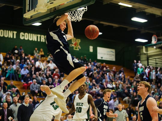 MMU's Tyler Muttilainen (11) dunks the ball during the Vermont state division I boys basketball semifinal game between the Mount Mansfield Cougars and the Rice Green Knights at Patrick Gym on Thursday night March 15, 2018 in Burlington.