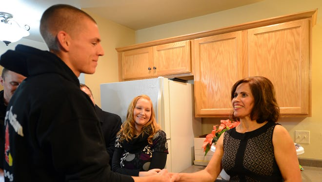 Blanca Villers, right, takes the keys to her new Habitat for Humanity home from De Pere High School construction trades student Alex Sulzer during the dedication ceremony December 19, 2014.