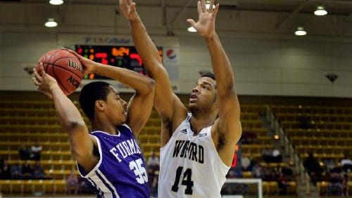 Furman's Daniel Fowler, left, is guarded by Wofford's Spencer Collins during last year's Southern Conference Tournament Championship. The two square off Saturday at Furman.