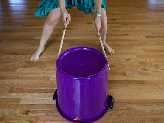 Instructor Winnie Purple beats a plastic drum during