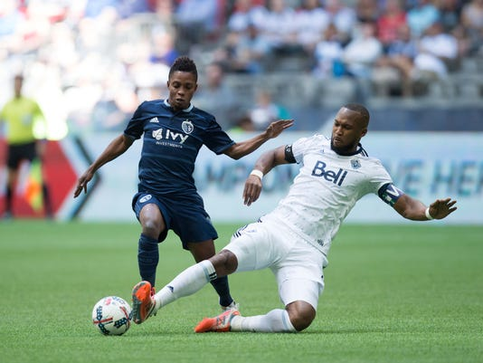 Vancouver Whitecaps' Kendall Waston, right, slides to take the ball away from Sporting Kansas City's Latif Blessing during the first half of an MLS soccer game in Vancouver, British Columbia, on Saturday May 20, 2017. (Darryl Dyck/The Canadian Press via AP)