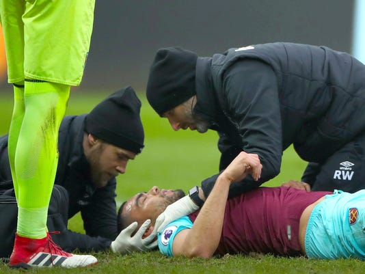 West Ham United's Winston Reid receives medical attention during the game against Swansea, during their English Premier League soccer match at the Liberty Stadium in Swansea, England, Saturday March 3, 2018. (Nick Potts/PA via AP)