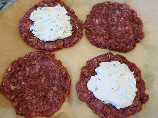 Boursin cheese is spread on half the burger patties; the other patties are placed on top to seal the cheese inside.