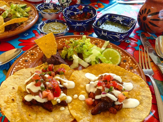 Pork tacos with chopped tomato and pineapples, and topped with creama, at Ariel's Cantina in Brookfield. Three varieties of salsa are served in beautiful Mexican salsa cups.