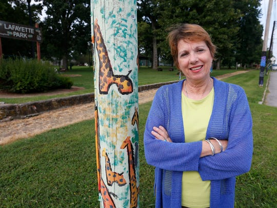 Zone 1 councilwoman Phyllis Ferguson stands in Lafayette Park near a painted utility poles that was part of a neighborhood-wide art project led by the Moon City Creative District.