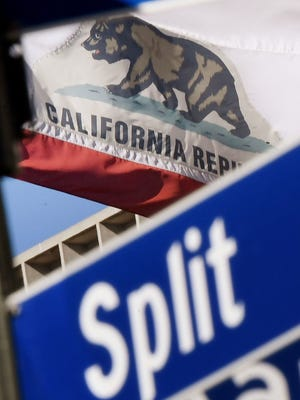The California State flag flies beside a sign for its sister city Split outside City Hall, in Los Angeles.