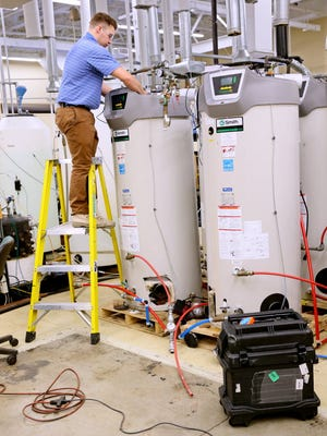 An engineer checks some A.O. Smith water heaters at the company's research and development facility in Milwaukee.