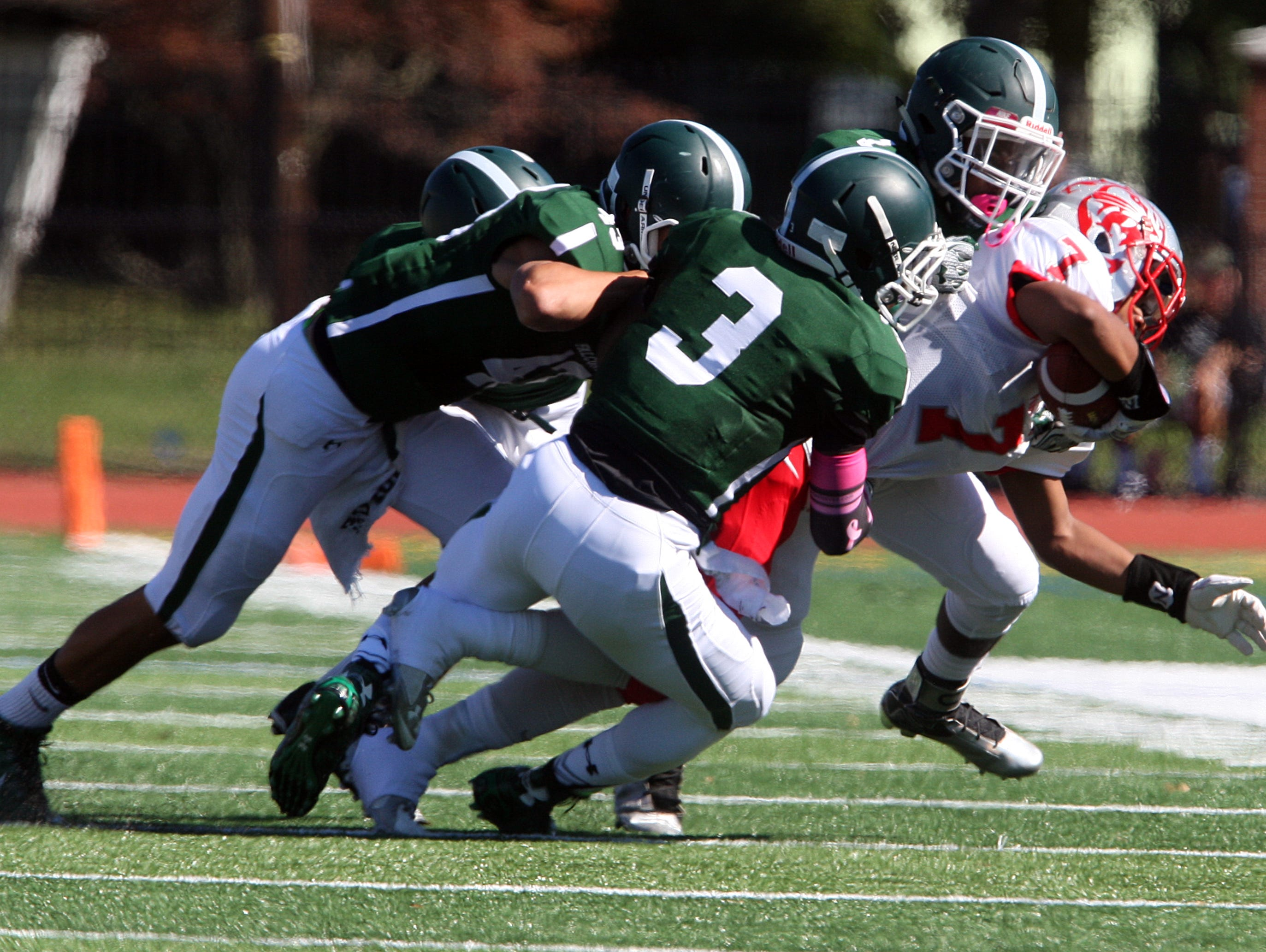 Action photos from the Perth Amboy High School at St. Joseph football game held at St. Joseph's new turf field in Metuhen on Saturday October 10, 2015. Here Perth Amboy's # 7 Josh Nazario is brought down by a trio of St. Joseph defenders.
