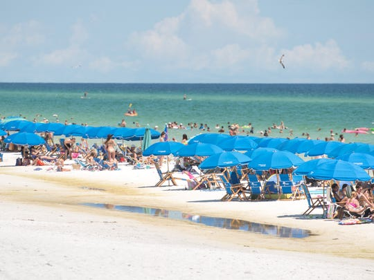 Beachgoers crowd the beach of Seaside in Walton County, Florida on Wednesday, July 19, 2017.