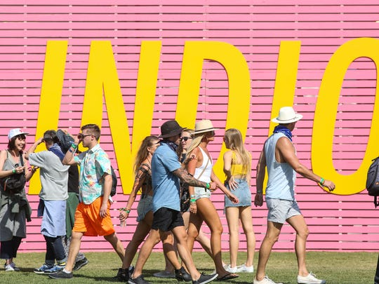 Apr 13, 2018; Indio, CA, USA;  Fans walk by a large Indio sign during the Coachella Valley Music and Arts Festival at Empire Polo Club. Mandatory Credit: Jay Calderon/The Desert Sun via USA TODAY NETWORK