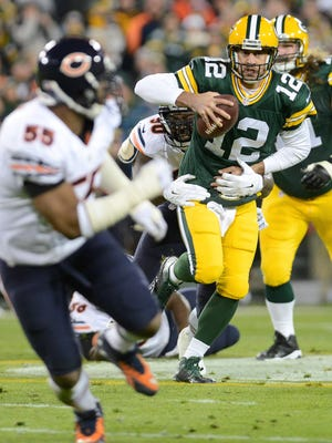 Green Bay Packers quarterback Aaron Rodgers (12) looks for a receiver to flick a pass to as he is brought down by Chicago Bears defensive tackle Jeremiah Ratliff (90).