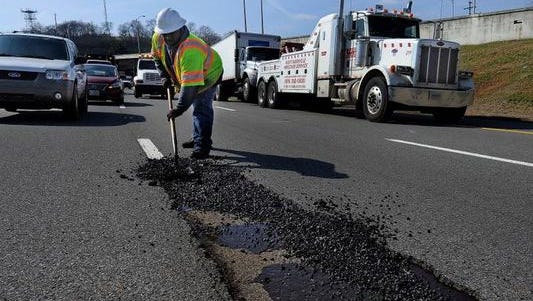 A TDOT worker fills in a pothole in Nashville. The holes have pocked interstates after the recent snow and ice.
