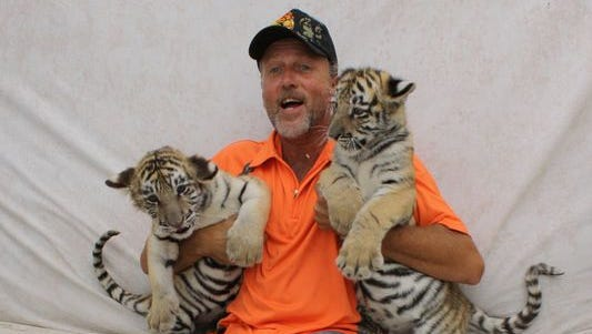 "Tim Stark, owner of Wildlife in Need Inc., hams it up with his tiger cubs Ockshay and Luush. ""It was awesome,"" said Tyler Brumley, 7, after holding a cub on his lap."